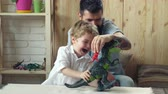imaginar : Father and cute little son playing toy dinosaurs. Dinosaur. Son and Father. Happy funny boy with father. The son and father play at home. A bearded man entertains his son.