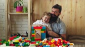 pistola : Father and son have fun time. Boy and bearded man play together. Family and childhood concept. Father and son with happy faces create colorful city with bricks.
