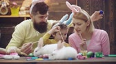 Mother, father and son are painting eggs. Happy family are preparing for Easter. Cute little child boy wearing bunny ears. Happy easter. Dostupné videozáznamy