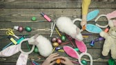 zając : Colorful easter eggs on wooden desk with live hares. Happy family are preparing for Easter. Close-up of family-friendly hands that feed hare on a wooden table with Easter eggs. Wideo