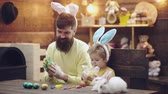 ovos : Father and son color the Easter eggs. Cute little child boy wearing bunny ears. Easter eggs on wooden background. Happy easter.