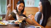 pauzinhos : Two Asian female friends eating and having a meal together. Women enjoying good time at Japanese restaurant
