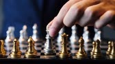 checkmate : Unrecognizable male in suit making a move in chess play against gray background Stock Footage