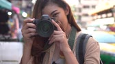 khaosan : Young Asian female tourist woman with smile holding a camera and taking photos in Bangkok, Thailand while travelling in Southeast Asia