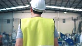 Close up rear view of factory worker with safety hard hat is walking through industrial facilities at heavy industry manufacturing factory