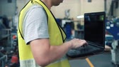 Close up of Industrial engineer in hard hat working with laptop in safety jacket at heavy industry manufacturing factory. Processing plastic injection molding industry