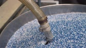 pellets : Vacuum loader hose sucking virgin plastic from tank in factory workshop