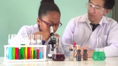 dirigieren : Young Asian scientist teaching African American kid how to use microscope with chemical substance tubes and flasks in classroom - science and learning education concept Videos