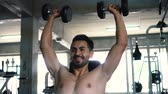 ćwiczenia : Muscular powerful young man doing shoulders overhead press lifting with dumbbells in fitness gym. Caucasian male fit model working out indoors