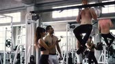 practising : Male and female friends cheering man practicing chin ups exercise on bars at the gym Stock Footage