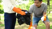bottiglie di plastica : Young teenage male and female group of volunteers with gloves collecting garbage waste into trash bag in green park. Environmental friendly and litter collection concept Filmati Stock