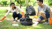 zwerfvuil : Young Asian man and woman wearing orange gloves and collecting trash in garbage bag in the park. Save the earth and environmental concern concept Stockvideo