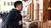 nadenken : Young Asian man tourist shopping and looking at souvenirs in Hallstatt Lake in Salzkammergut during trip to Austria, Europe