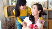 neşe : Smiling happy Asian teenage daughter and Asian middle-aged mother hugging together in indoor living room at home. Mum is holding a present gift. Stok Video