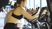 lovaglás : Attractive Asian woman riding on the spinning bike at the gym and looking at camera. Healthy and weight loss lifestyle