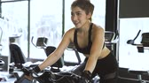 lovaglás : Beautiful Asian woman riding on the spinning bike at the gym. Healthy and weight loss lifestyle Stock mozgókép