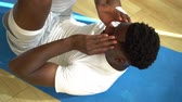 복근 : Young African American man doing sit-up exercise on yoga mat at gym. Male fitness model performing crunch at fitness center.