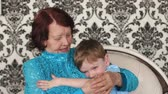 family values : Happy grandmother hugging her grandson, slow motion. Portrait of happy grandmother and grandson.