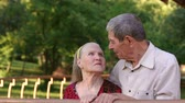 прочный : Portrait of elderly grandparents in the Park gazebo, slow motion. Grandma and grandpa look at each other with tenderness standing in a Park.
