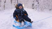 nature close up : Little boy in winter clothes sitting in a sled in winter outdoors.