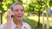 nature close up : Gray-haired grandfather eighty years talking on the phone in Park on a background of green grass. Close-up. Slow motion. Portrait of a grandfather with the phone in Park. Stock Footage