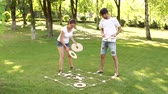 кресты : Two young people play the game tic tac toe big pieces in the Park in the summer. Large outdoor games.