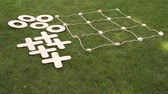 tık : Close-up of a big game of tic tac toe lying on the grass in the Park. Large pieces of crosses and toes.