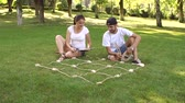 tık : Two friends play big TIC TAC toe while sitting on the grass in the Park. A guy and a girl are playing active logic games outdoors in the summer.