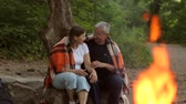 entrar : Happy elderly couple sitting together in a blanket by the fire on the nature.