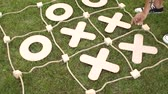 tık : Two children play in a giant TIC TAC toe in summer camp. Close-up. Slow motion.