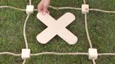 tık : Close-up of a girl playing in a large tic tac toe on the grass in summer Park. Great logic game. Girl puts a cross on field of play in tic tac toe. Stok Video