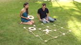 tık : Two friends play big tic tac toe while sitting on the grass in the Park. A guy and a girl are playing active logic games outdoors in the summer. Stok Video