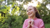 forest : Portrait of happy smiling little girl at sunset in the woods. Portrait of happy little girl 10 years in a Sunny Park on a background of green trees. Stock Footage