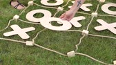 tık : Close-up of a boy playing in a large tic tac toe on the grass in summer Park. Great logic game. Active rest in the summer. Stok Video