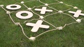tık : Close-up of the winning scenario of the game TIC TAC toe on the grass in the Park. Large figures of the game TIC TAC toe. Stok Video
