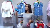 baby store : Pregnant woman choosing Baby clothing in baby and maternity shop. A young pregnant girl is shopping at a childrens clothes and accessories store, she is holding blue and pink booties. The choice. Stock Footage