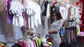 baby store : Portrait of a pregnant girl in a childrens shop. Young happy pregnant woman choosing newborn clothes at the baby shop store.