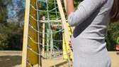 snění : Close-up of a pregnant woman stroking her large belly against the background of a playground and a childrens roller coaster.