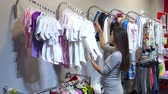 baby store : Pregnancy, people, sale and expectation concept - happy pregnant woman shopping and buying baby bodysuit at children clothing store.