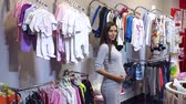 těhotná : Portrait of a modern young pregnant girl in a childrens clothing store.