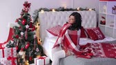 örgü : A beautiful sexy girl in a warm knitted sweater sits covered in a blanket on the bed near the decorated Christmas tree.