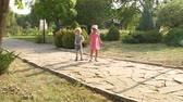 dráha : Two young children walk in the Park along the stone alley on a hot summer day at sunset. Slow motion. Dostupné videozáznamy