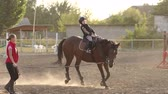 klusat : Little girl riding a horse, learning and training in the riding school. Little girl learns riding with a trainer at ranch. Slow motion.