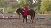 klusat : A female coach helps a child to climb a horse, learning to ride a horse at a horse farm. Children are engaged in horse riding. Slow motion. Dostupné videozáznamy