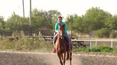riding arena : Teenage girl with excess weight rides a brown horse on a horse farm at sunset. Slow motion. Stock Footage