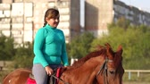 riding arena : Teenage girl with excess weight sits a brown horse on a horse farm at sunset. Slow motion. Stock Footage