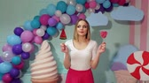 arbuz : A young girl in bright clothes with lollipops in her hands in a studio with balloons, marshmallows and ice cream, she can not choose one lollipop of two.  Candy girl. Wideo