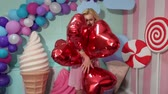 lízátko : Cute girl in pink striped dress with blonde curly hair holding a lot of red balls in the shape of hearts on the background of huge sweets. Dostupné videozáznamy