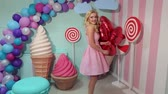 lolipop : A happy girl in a pink dress is holding a lot of red balloons and is spinning around herself in the studio with a sweet interior.