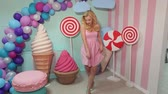 lolipop : A glamorous fashion girl in a pink dress poses in the studio against a background of colorful balls and huge lollipops and marshmallows.
